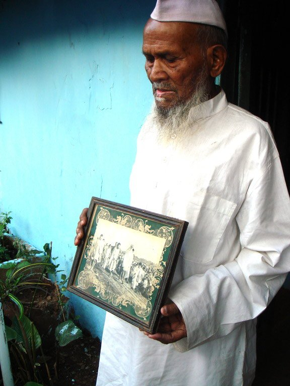 Old man with frame in hand