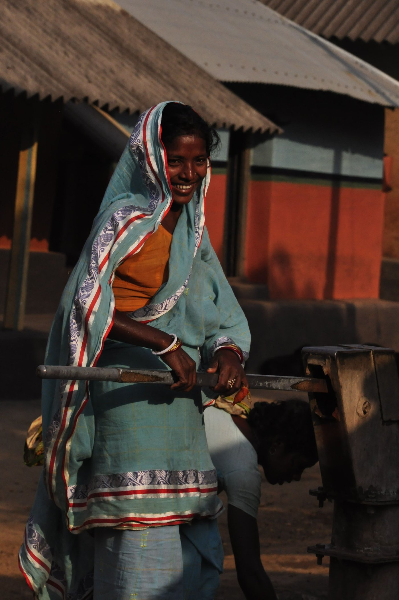 Santhal woman pumping a tubewell to collect water