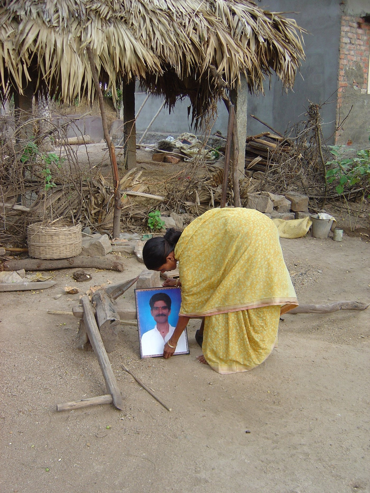 Woman putting her husband's photo on the ground
