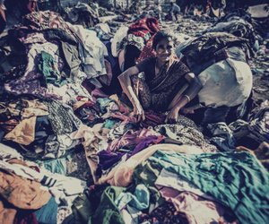 Vaghri woman, sitting amidst used clothes