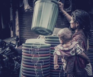 Woman with baby holding plastic bucket