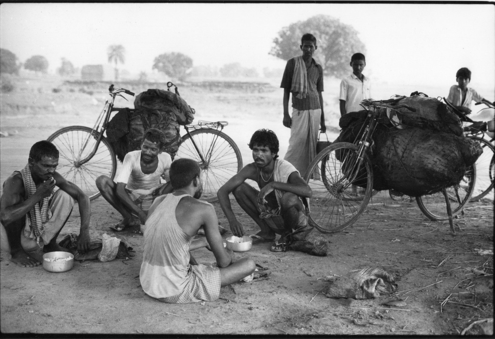 Group of men from different castes eating lunch beside their coal laden cycles