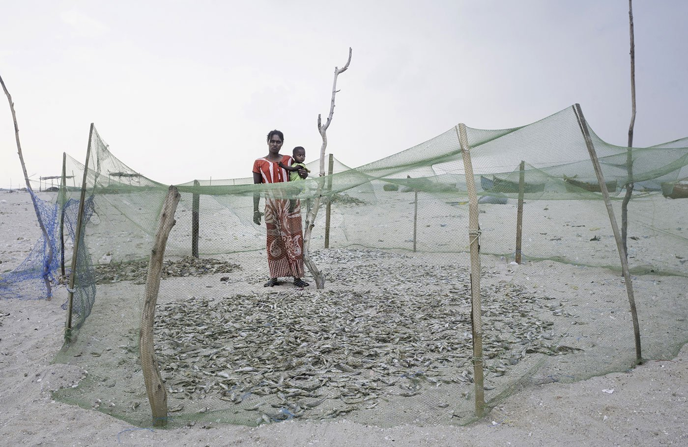 Woman with baby standing behind fishing nets used for drying fish
