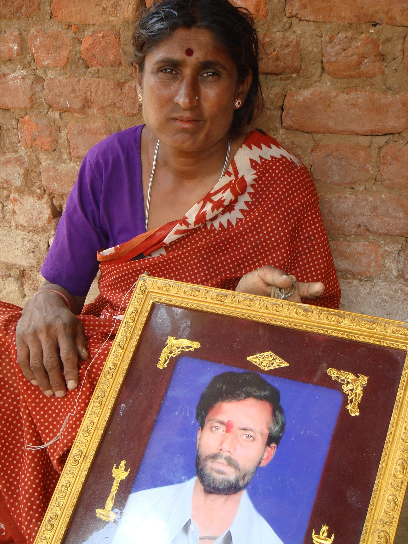 Jayalakshmamma holding the photo of her deceased husband