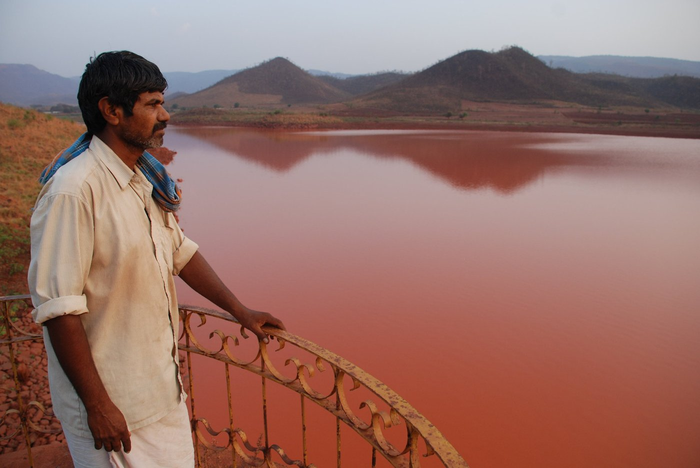 Man looking out to polluted reservoir