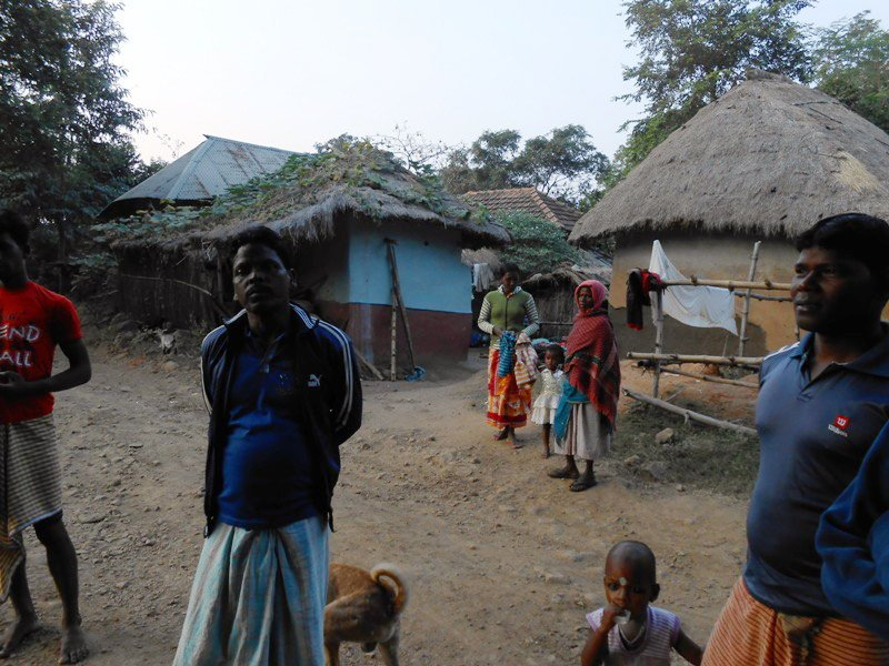 Group of people standing in front of huts as man looks into the camera