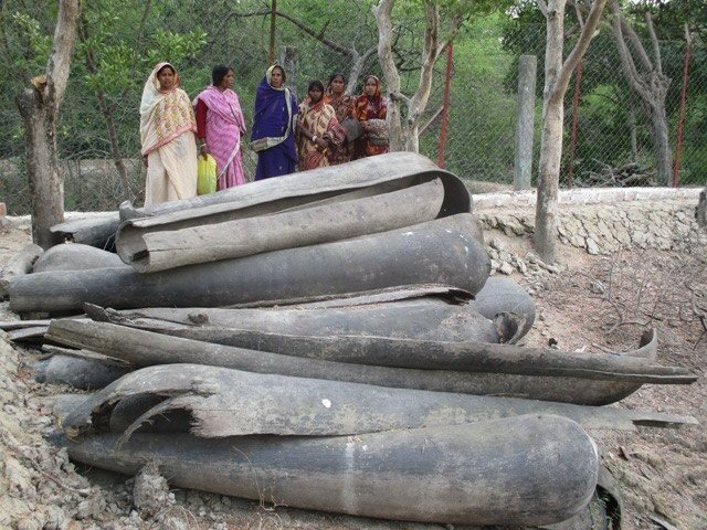 A group of women standing in front of broken canoes