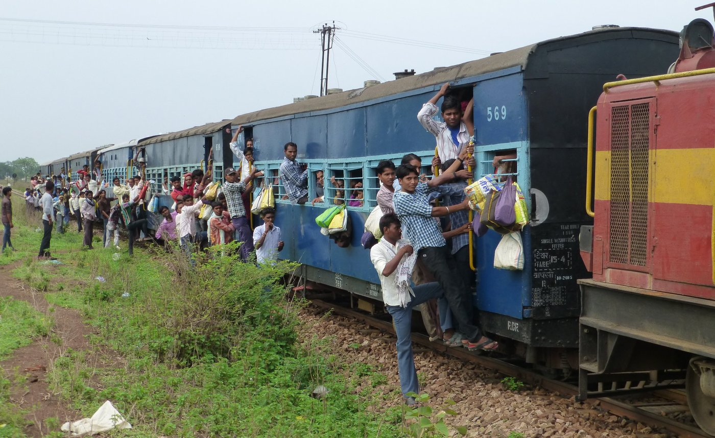 Crowds of people travelling on a overcrowded train