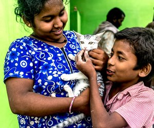 Kavita, 16, and her brother, Anil, around 12, find solace with Honey, their cat
