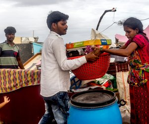 P. Jagadeesh and his pregnant wife, P. Mabbi, trying to salvage their belongings from the rubble